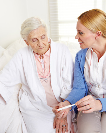 Geriatric nurse with fever thermometer and senior patient at home photo