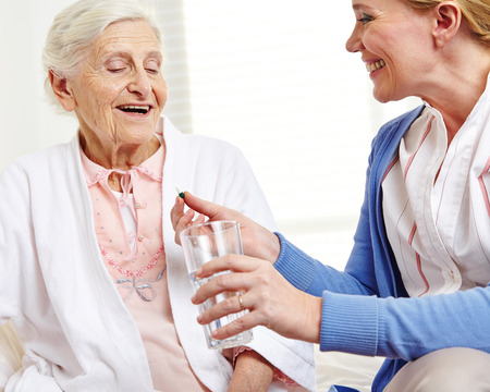 Senior woman taking pill with water from geriatric nurse