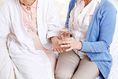 Senior citizen woman getting pill with water from a nurse photo