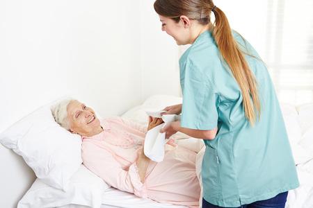 utiles de aseo personal: Lavado enfermera geriátrica mujer postrada en la cama superior y secándose las manos en el hogar de ancianos