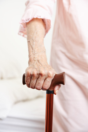 Wrinkly hand of senior woman with walking cane photo
