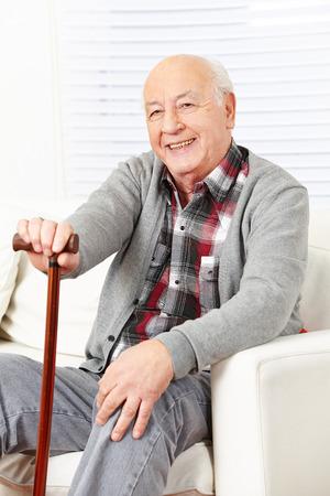 Gelukkige oude man met stok om thuis te zitten op een sofa Stockfoto