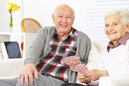 Happy senior citizen couple playing cards at home photo