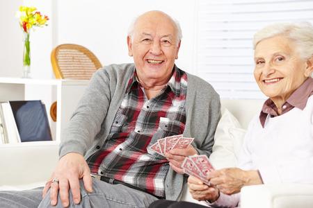 jeu de cartes: Senior couple de citoyens heureux cartes � jouer � la maison