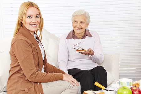 Senior woman and caregiver eating breakfast together at home photo
