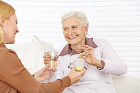 Senior citizen woman getting medical pill with water in a retirement home photo
