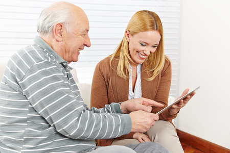 citizen: Happy family with senior citizen using a tablet computer