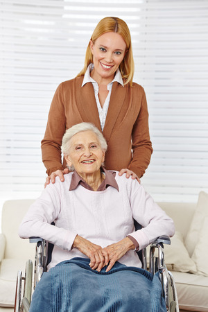 Happy family with woman and senior citizen in a wheelchair photo