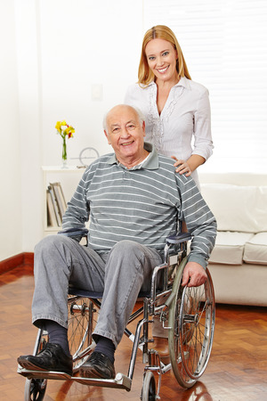 Smiling woman with her old senior father in a wheelchair at home photo