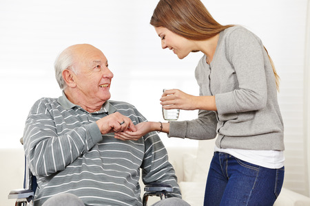 Woman giving senior man in wheelchair medical pill with a glass of water photo