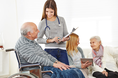 retirement homes: Caregiver doing survey with senior citizens in a nursing home Stock Photo
