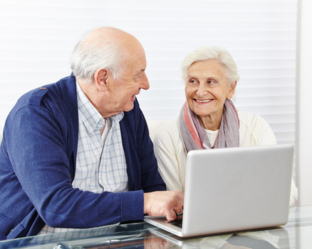 Happy senior couple shopping in internet with laptop computer photo