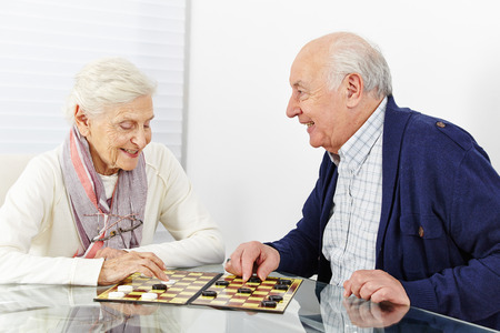 board game: Happy senior couple playing checkers together in a retirement home