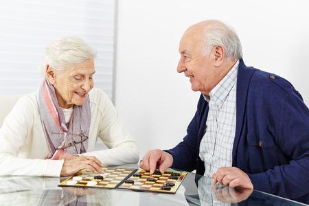 Happy senior couple jouant aux dames ensemble dans une maison de retraite
