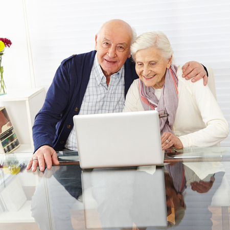 Happy senior couple using the internet together with a laptop computer photo