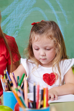 Girl drawing with many colorful crayons in a\ kindergarten