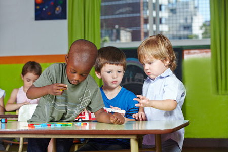 playschool: Children playing together in kindergarten group with building blocks and a firetruck