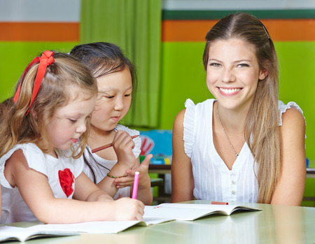 Happy nursery teacher with kids drawing in a kindergarten photo