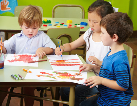 tempera: Three children painting with watercolor on paper in a kindergarten