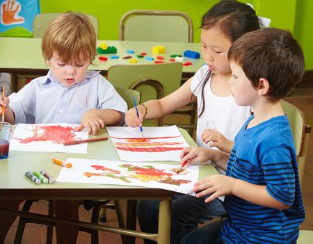 Trois enfants peinture à l'aquarelle sur papier dans une école maternelle Banque d'images - 26793511
