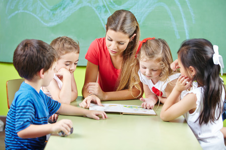 Kleuteronderwijzer leesboek voorgelezen aan kinderen in een kleuterschool groep