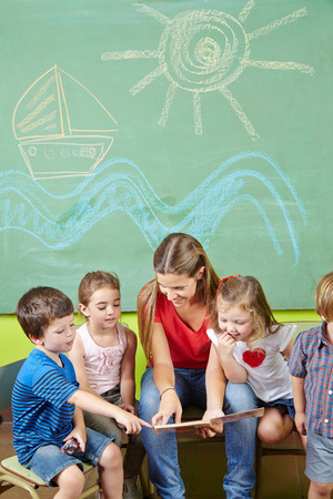 maestra preescolar: Los niños en la lectura de libros de preescolar, junto con un profesor de guardería