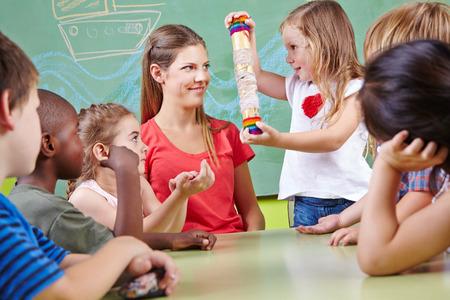 유치원에서 음악 교육에있는 아이들은 레인 메이커의 악기와 연주