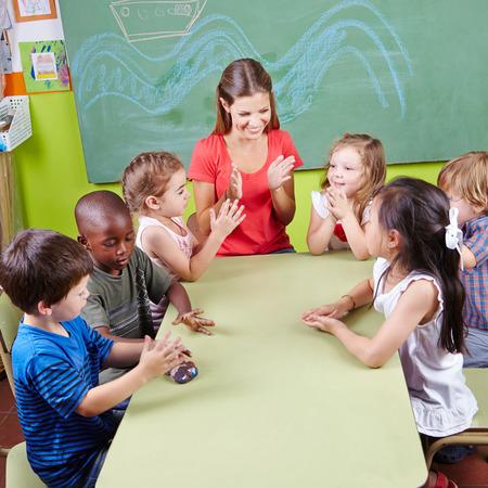 divertirsi: Gruppo di bambini battendo le mani nella scuola materna in classe di educazione musicale Archivio Fotografico