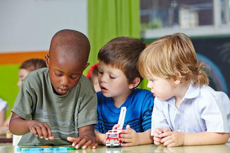 Drie kinderen in de kleuterschool spelen met bouwstenen en auto's Stockfoto
