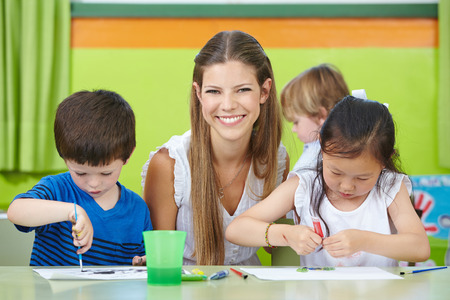 CHILD CARE: Happy child care worker with children drawing in a kindergarten Stock Photo