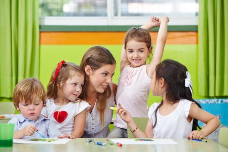 children talking: Children talking to nursery teacher in kindergarten while painting pictures