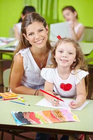 Happy child care worker helping girl painting in a kindergarten photo