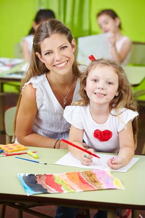 maestra preescolar: Trabajador de cuidado de niños feliz ayudando pintura niña en un jardín de infantes Foto de archivo