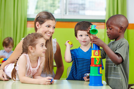 women children: Children with nursery teacher building tower in a kindergarten group
