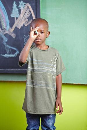 garcon africain: Garçon africain debout à la craie devant latté dans un jardin d'enfants
