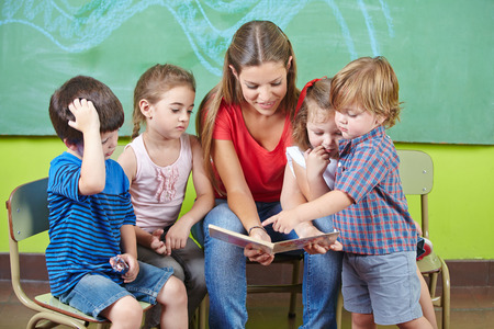 bambin: Enfants et pu�ricultrice livre de lecture ensemble � la maternelle
