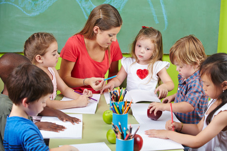 pedagogy: Children learning writing together in preschool with nursery teacher