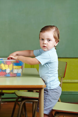put away: Boy helping to clean up toys in a kindergarten Stock Photo