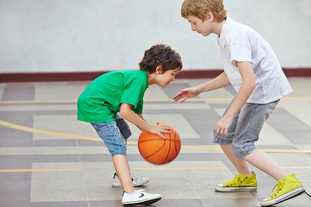 Zwei Jungen spielen zusammen Basketball auf dem Schulhof einer Schule