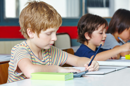 left handed: Lefthanded boy in elementary school writing with a pencil