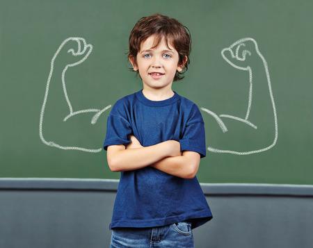 Sterke kind met spieren getrokken op bord in basisschool Stockfoto