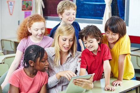 elementary school: Teacher using digital media on tablet PC in elementary school class
