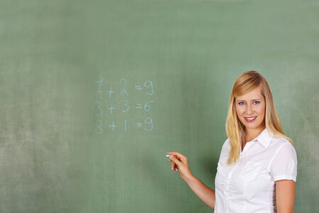 traineeship: Teacher writing math problem on a chalkboard in elementary school Stock Photo