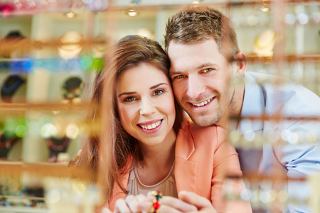 Happy smiling couple in jeweler store buying jewelry photo