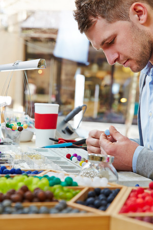 Man making apprenticeship as artisan in a jewelry workshop photo