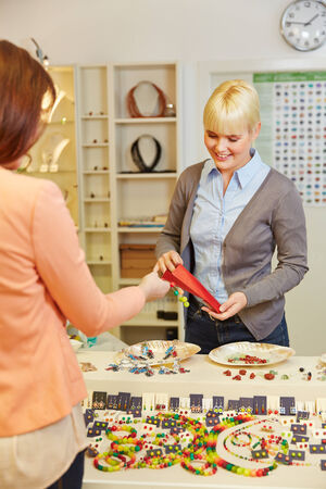 Woman buying jewelry in store from a juweler photo