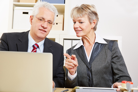 hint: Business woman helping colleague with his laptop computer in the office
