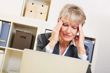 Elderly business woman sitting with burnout in he office at the desk photo