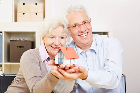 tenant: A happy senior couple holding a small house in their hands