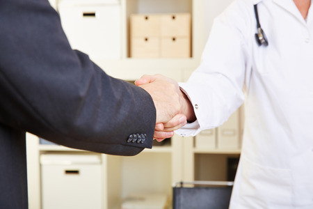 consultant physicians: Handshake between doctor and patient in an office